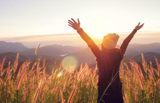 A young woman, arms upraised, looking at the sunrise. Automatic Renewal helps save time, money and effort.