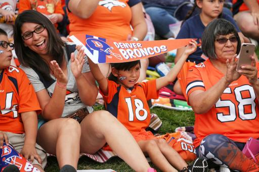 A family cheering on the Denver Broncos