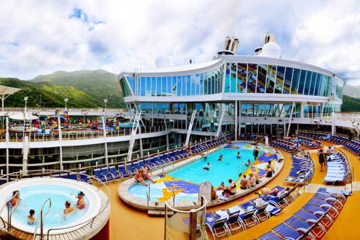 The deck of Royal Caribbean's Enchantment of the Seas with a pool and deck chairs.