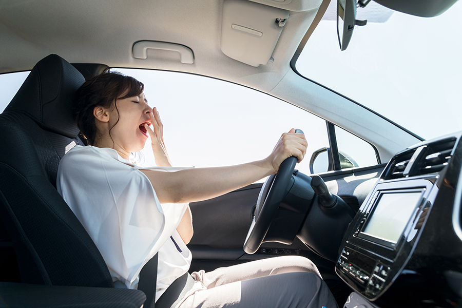 woman yawning behind the wheel of a car.