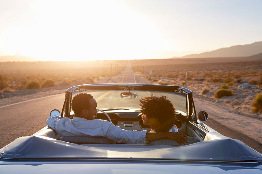 A couple in a convertible on a road trip